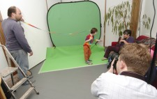 Director Liz Crow gives directions to a boy dressed in a multicolored rainbow t-shirt and brown trousers who stands in front of a greenscreen. He carries a long fabric ribbon in rainbow colours which is being held aloft at the other end by Bryan to look as though it is streaming in the breeze. Matt has his back to the camera.