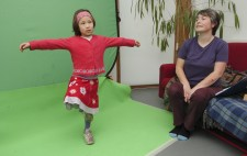 Maia stands on one leg with her arms outstretched, looking dreamily, in front of a greenscreen. Liz sits on a sofa just to the side.