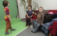 Against a greenscreen, a boy of about six stands in position, looking towards Liz who is talking to him. Two of the other children sit next to her on the sofa.