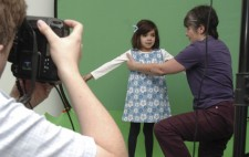 Against a greenscreen, a girl of around five years old stands facing towards the camera dressed in a white top and blue flowery pinafore, a blue ribbon in her hair. Liz kneels to her side, gently moving her arms into position.