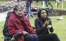 At the lakeside, Director Liz Crow sits in her wheelchair in a red raincoat and scarf, a sign language interpreter seated next to her. In the background, the jimmy jib is being prepared for the filming the big race.