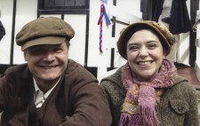 At the lakeside, James and Poppy beam at the camera. James is dressed in a brown suit and cap, whilst Poppy wears a vintage hat with a modern sweater and scarf covering her 1930s summer dress.