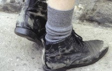 A close-up of a pair of feet in some scruffy black shoes and grey ankle socks.