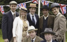 Seven members of the cast from the lakeside shoot pose together for a photo, all dressed in period costume, Union flag bunting festooned behind them. The men wear suits and the woman is wearing a yellow dress and a white overcoat. All wear boaters, fedoras or caps.