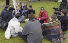 Director Liz Crow sits on the lakeside grass surrounded by the swimming lads and members of the crew