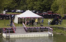 A white marquee stands behind the swimming pontoon, which is decorated but still empty of actors. The crew are on the banks preparing to shoot, with camera tests taking place.