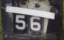 A battered blackboard with the words 'Water Temperature' painted on in white. Two metal labels in the centre of the board read '56'.