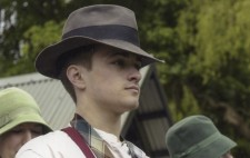 A cast member waits on set between lake scene takes, a loose tie around his neck and a brown fedora on his head.