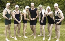Seven male swimmers stand in a row pulling poses. Each wears a woollen swimming costume that covers their entire torso and a swimming cap with chin strap.