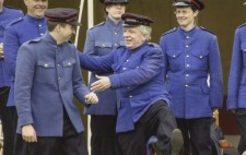 Dressed in royal blue overcoats and military-style caps, five members of the band, one with his leg raised high, share a joke between takes.