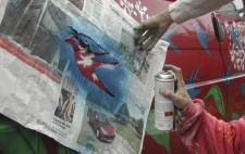 A close up of a hand holding a newspaper stencil of a silhouetted bird against the side of a red VW camper van. Another hand sprays aerosol paint onto the paintwork to add a bluebird to the leaves and sprays of white flowers already adorning the vehicle.