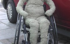 A life-sized hessian fabric doll with no features sits naked on a manual wheelchair next to a red van.
