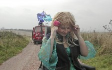 An a country lane with grassy banks, and against a looming sky, Liz Crow is dressed in the same green dress and wig, a flower in her hair and a navy blue gilet added for warmth. In the background is the red van with its spray painted decoration, Liz's wheelchair perched high on its rooftop, with fabric billowing in the wind.