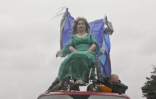 Against a looming sky, Liz Crow, perched on the roof of the van, her wheelchair strapped in place, is dressed in the same green dress and wig, fabric flowing from the back of her chair. Lying flat along the roof of the van are two of the crew holding tightly to the chair for additional anchorage.