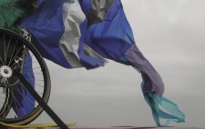The rear wheel of a wheelchair is strapped to the roof of a red ban, a great train of blue, grey and purple ripstock fabric billowing in the wind against a solid grey sky.