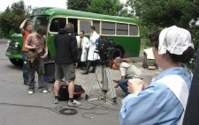 Photograph: A green vintage bus is in the background, a camera set up and crew busily preparing for a shot. Two white-coated orderlies stand near the bus. Terry looks skywards. In the foreground the nurse holds a cup of tea and watches the preparations.