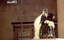Another SkyARTS screenshot. Liz, seated on her wheelchair, pulls away the white sheet to reveal black Nazi uniform, with its red swastika armband.