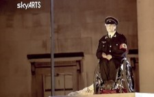 A close-up screenshot, the SkyARTS logo in the top left corner, shows Liz on her wheelchair on the plinth and wearing a black Nazi uniform.