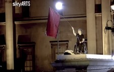 A SkyARTS screenshot shows Liz, on her wheelchair and dressed in a plain black t-shirt, holding aloft a large red flag with black text.