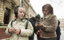 A primary age boy stands at the edge of the Square wearing a backpack and large earphones, whilst Jo sets the handheld computer.