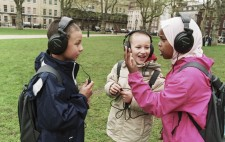 Three primary age children stand in the grassy Square, wearing large earphones and excitedly exchanging their experiences of 1831 Riot!