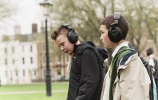 Two primary age school boys wearing large earphones stand in the grassy Square deeply absorbed in the audio.