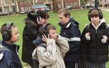 Four primary age children and a teacher stand in a grassy area of the Square wearing large earphones, each absorbed in the audio and looking to different areas of the Square.