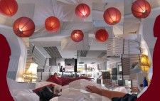 A montage of photos giving a panoramic view of Liz's view from the bed: two standard lamps frame the bed with a warm yellow glow, the space extends beyond the foot of the bed to a cafe area, the words 'cafe' lettered on a large picture window. Above the bed is a fabric canopy in white, festooned with multiple red paper lamp shades. Liz's arm extends across the sheets.