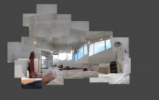 A montage of photos giving a panoramic view of Liz's view from the bed: white walls and a ceiling dotted with lights, an open door to the room, with two large high windows on the wall opposite. Liz's arm extends across the sheets.