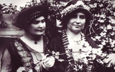 A portrait of the two women in mid-life. They are elegantly dressed in late Edwardian fashion, both wearing hats, and standing against a backdrop of a hedge of white blossom.