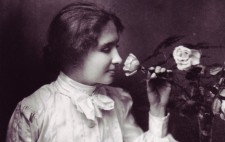 Helen wears a white Edwardian blouse with wide sleeves and a tie bow at her neck. With her left hand, she pulls a rose to smell, while her right rests upon a Braille book on her lap.