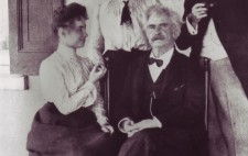 Helen and Mark Twain (Samuel Clemens) sit on chairs. He faces the camera and she is turned towards him. Helen wears a floor-skimming dark skirt and a white blouse with high collar. Behind her stands Annie, her hand resting on Helen's raised palm to fingerspell the conversation. Behind Twain, another (unidentified) man stands, pipe in hand. The photograph is signed 'SL Clemens.'