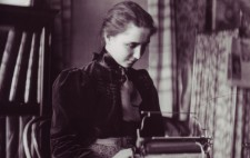 Helen sits at a desk before a Braille typewriter. Her hair is pulled back from her face into a braid and she wears a dark blouse with a high next and large bow.