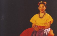 Against a pitch black backdrop and seated on a black bench, Isolte is dressed in a bright yellow, short-sleeved shirt and long, flowing, orange skirt, with a purple sash. Brightly coloured flowers are woven into her hair and she is adorned with jewellery: large, chunky earrings, necklace, bracelets and rings.