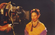 A close up of Isolte, dressed in bright yellow top, with a purple shawl around her shoulders and flowers in her hair. A large film camera is focused on her as she sits against a pitch black backdrop and looks directly into the lens.
