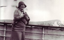 Standing at a ship's rail, land in the background and a seagull overhead, Helen smiles broadly and holds her hands together in front of her chest. She is dressed in late 1930s fashion, a calf-length skirt, silk scarf tied around her neck, a cloche hat and sturdy shoes.