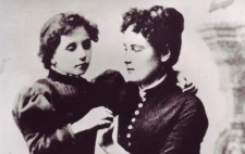 Dressed in late Victorian gowns, Helen, aged about 8, stands next to a seated Annie, in her 20s. Helen drapes an arm around her neck and Annie fingerspells onto her other hand and looks tenderly at her pupil.