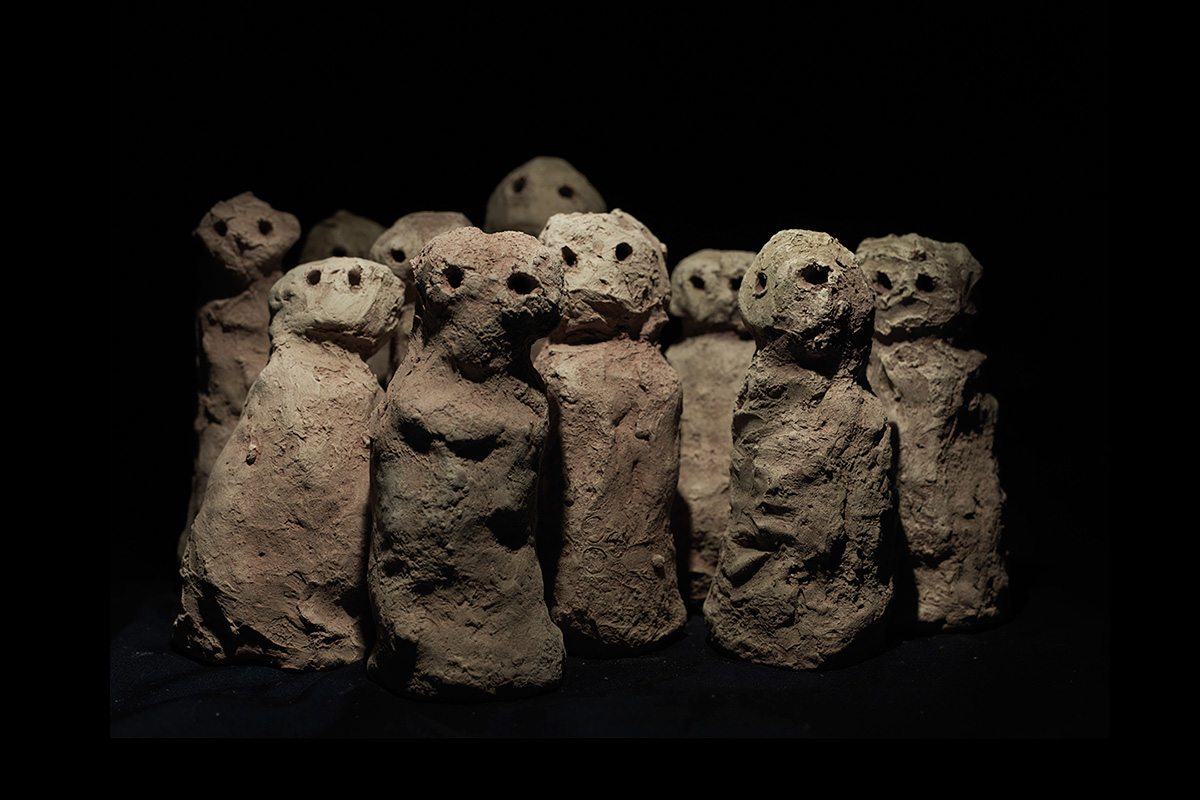 Against a pitch black background is a huddled group of ten small clay human figures, dried and fired to soft terracotta. The figures are in very simple form: head and body, each with two dark eyes gazing out to the viewer. Each is sculpted to the same form, yet differs in the character it conveys.