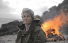 Liz Crow looks to camera. Behind her, the bonfire roars in orange flame against a backdrop of beach shingle and bolders.