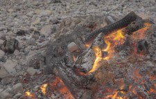 The embers glow, the last few flames flickering. At the out edges, the figures are visible, encased in chicken wire, merging into the surrounding shingle.