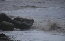 Waves roll towards beach boulders.