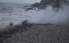 Out of shingle, seaweed and seawater billows steam.