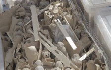 The figures are stacked in rows, each wrapped in paper. They are surrounded by chicken wire, held in place with plastic crates and scattered with pieces of kindling.