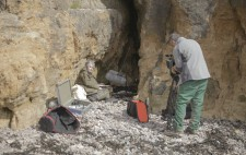 In the shelter of a hollow in the rocky cliff-face, Liz sits on beach stones, facing towards a large fluffy microphone on a stand. Nearby a camera operator sets up a camera on a tripod.