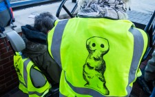 A member of the production team wears a high vis jacket with the Figures logo, a drawn figure, and the text #We Are Figures.