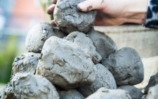 A hand adds another clump to a mound of clay.