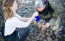 Liz drinks from through a staw, as her PA extends a blue water bottle. Liz holds a piece of clay, a heap of clay still remaining to be sculpted.