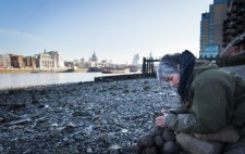 On a wide shingle foreshore, St Paul's and the London skyline as a backdrop, Liz leans over a pile of clay, sculpting a figure.