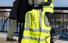 On the back of an empty wheelchair is a high vis jacket with the Figures logo, a drawn figure, and the text #We Are Figures. In the background, a member of the production team leans against the foreshore railing in conversation with audiences.