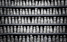 Over 100 small clay figures are lined up over five rows of shelving. Each is sculpted to the same design, yet varies in the detail, giving a sense of commonality and individuality.